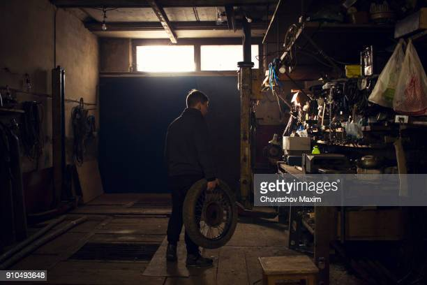 mechanic carrying vintage motorcycle wheel in workshop - desaturated stock pictures, royalty-free photos & images