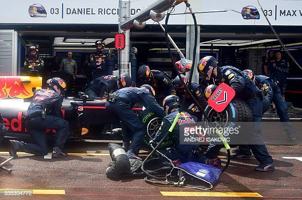 Mechanic change tires on the car of Infiniti Red Bull Racing's Australian driver Daniel Ricciardo in the pit lane at the Monaco street circuit on May...