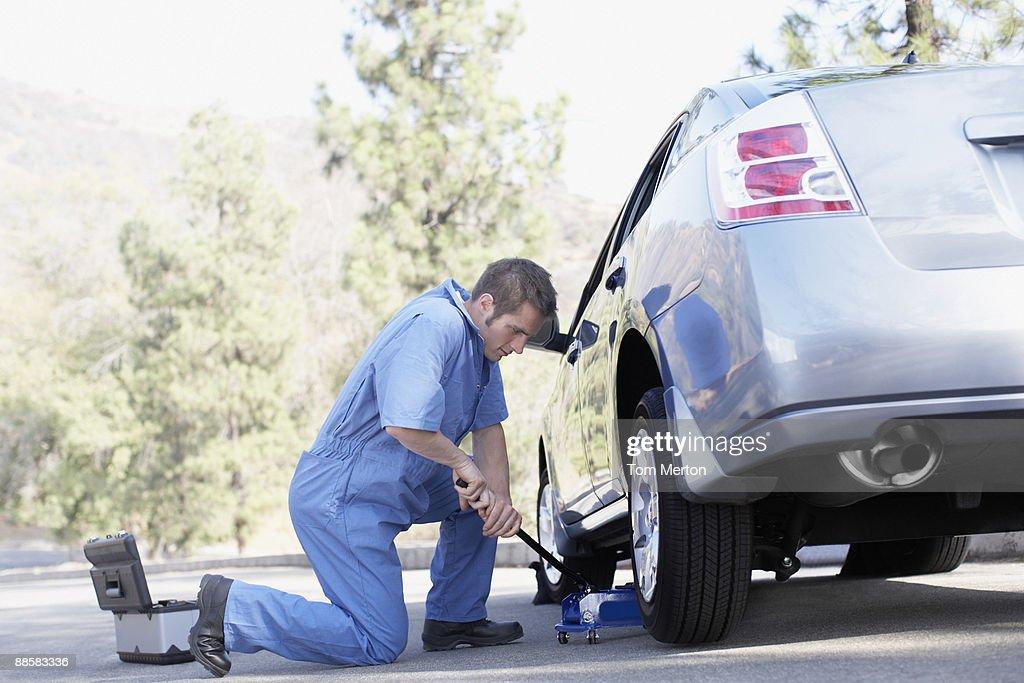 Mechanic changing car tire : Stock Photo