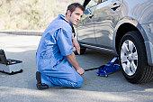 Mechanic changing cars flat tire