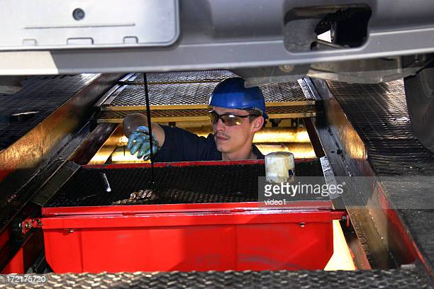 mechanic changing oil under a car - oil change stock pictures, royalty-free photos & images
