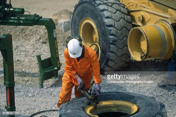 Mechanic changing tyre on heavy duty articulated dumper truck,.