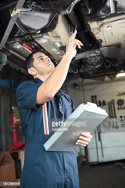 Mechanic checking a car with clipboard