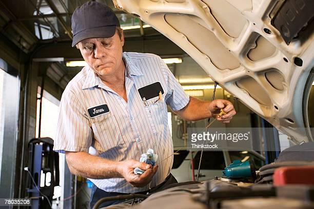 Mechanic checking dipstick