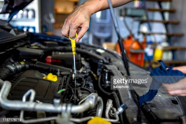 mechanic checking oil - auto repair shop stock pictures, royalty-free photos & images