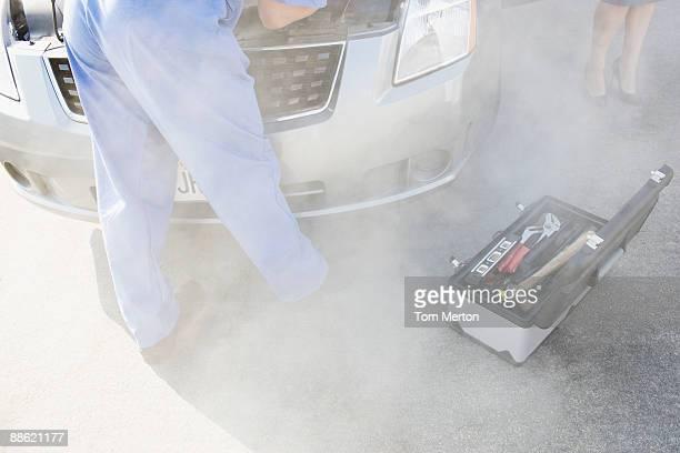 Mechanic checking smoking car engine