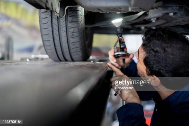 mecânico que verifica o alinhamento do carro que verific o abismo usando uma lâmpada - foco determinação - fotografias e filmes do acervo
