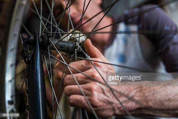 Mechanic cleaning bicycle nut in workshop