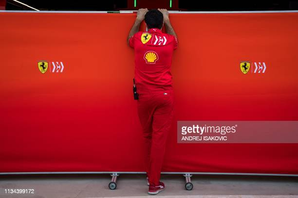 TOPSHOT A mechanic closes the garage as Mick Schumacher prepares to drive his first laps for Ferrari at the inseason test at the Sakhir circuit in...