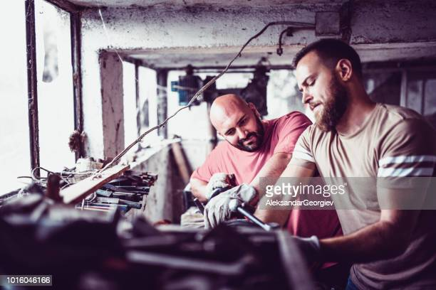 Mechanic Colleagues Working Together On Fixing Parts In Workshop
