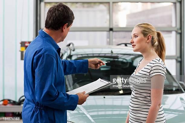 Mécanicien discuter de voiture avec jeune femme