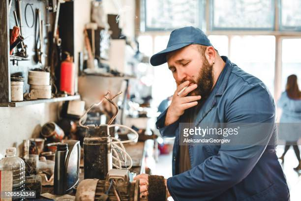 mechanic enjoying a smoke while working on car part - strike industrial action stock pictures, royalty-free photos & images
