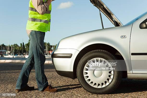 Mechanic evaluating car breakdown on side of road