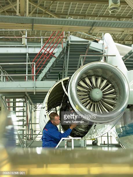 Mechanic examining aircraft in hangar
