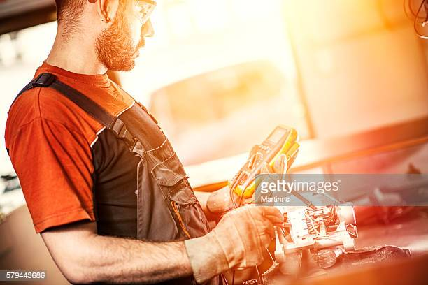 mechanic examining electric motor with voltmeter in a workshop - electric motor stock photos and pictures