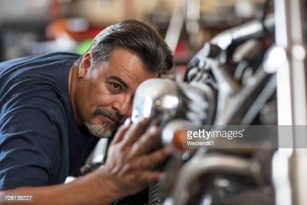 Mechanic examining motorcycle in workshop