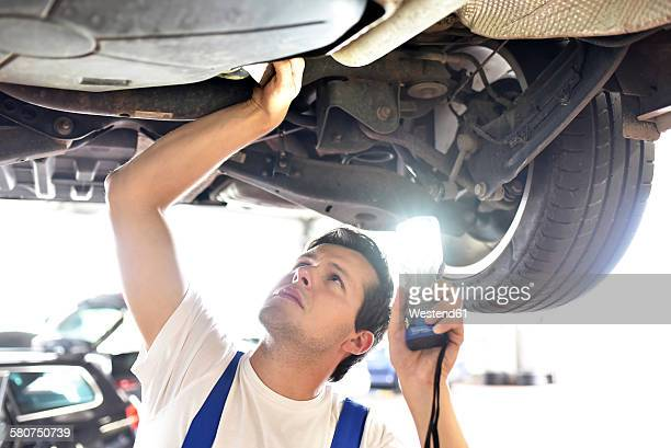 Mechanic examining underbody of a car in a garage