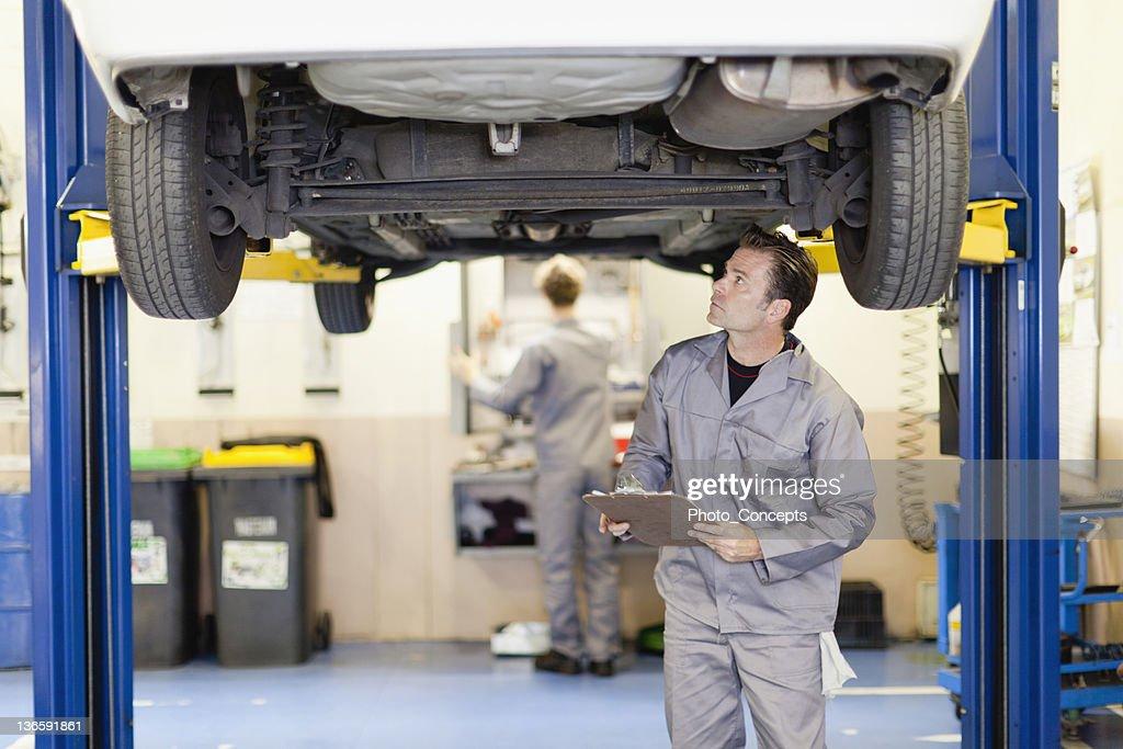 Mechanic examining underside of car : Stock Photo