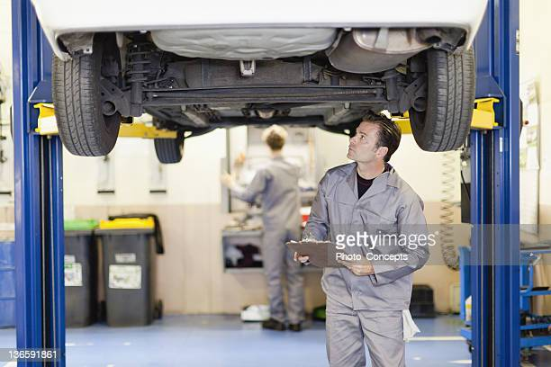 Mechanic examining underside of car