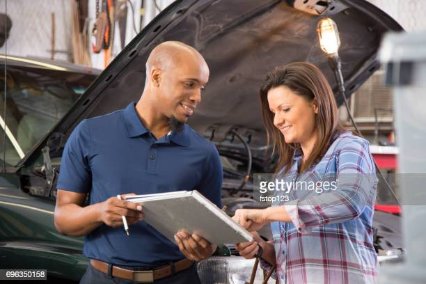 Mechanic explains vehicle repair invoice to customer, auto repair shop.