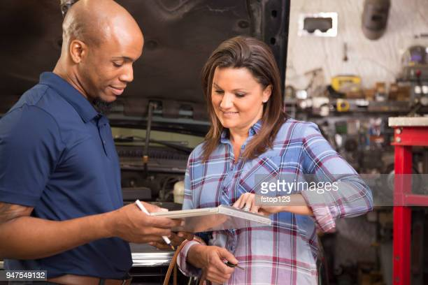 Mechanic explains vehicle repairs to customer in auto repair shop.