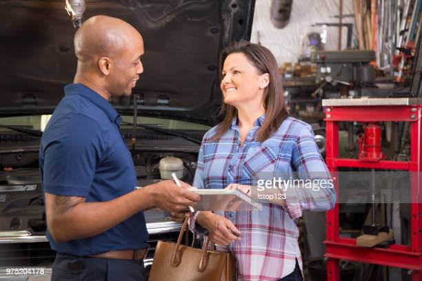 Mechanic explains vehicle repairs to customer in auto repair shop.