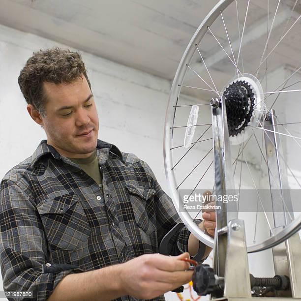 Mechanic fixes spokes on bike wheel
