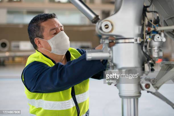 mechanic fixing an airplane while wearing a facemask - air vehicle stock pictures, royalty-free photos & images