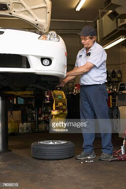 Mechanic fixing car on lift