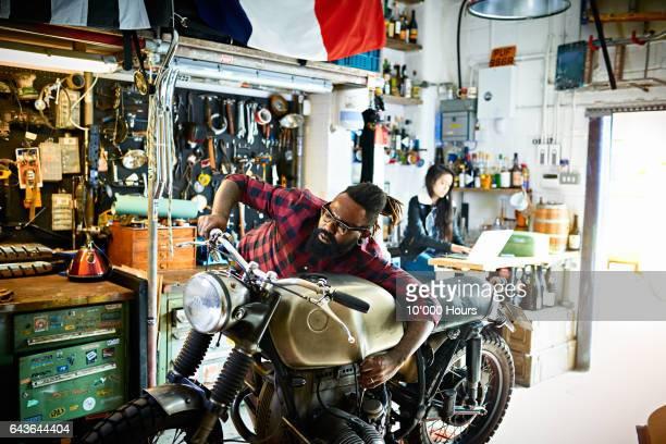 Mechanic fixing motorcycle in workshop.
