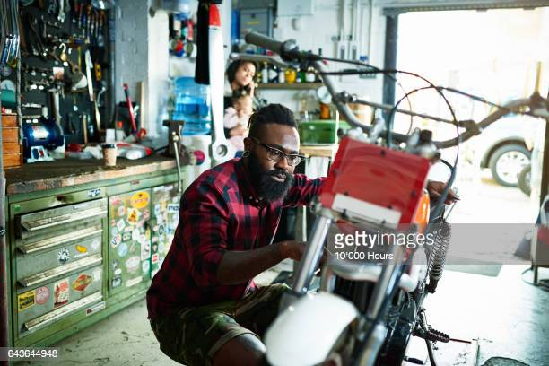 mechanic fixing motorcycle in workshop. - only mid adult men stock pictures, royalty-free photos & images
