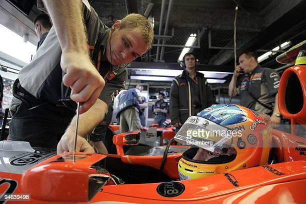 Mechanic for the Spyker MF1 team fixes the mirror on Adrian Sutil's car during the first practice day for the Formula 1 Japanese Grand Prix in...