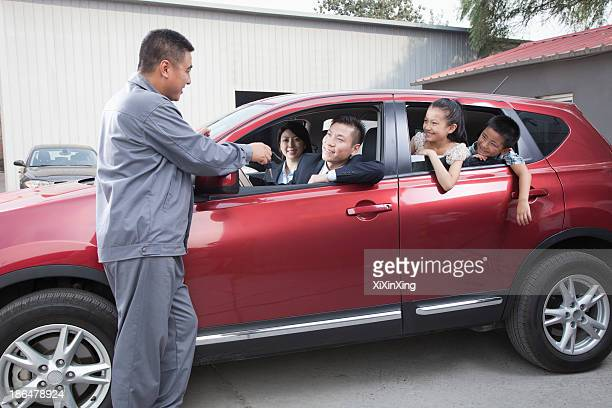 mechanic giving car keys to family - auto repair shop exterior stock pictures, royalty-free photos & images