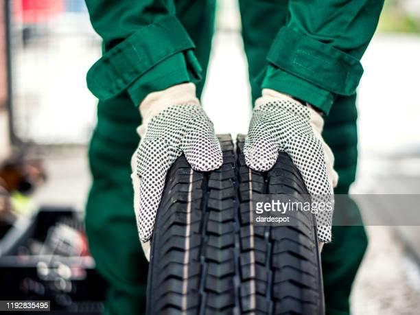 タイヤを押すメカニックハンド - タイヤ ストックフォトと画像
