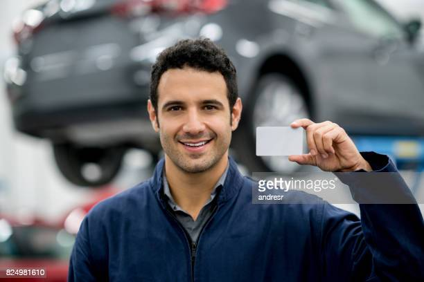 Mechanic holding a business card at an auto repair shop