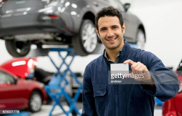 Mechanic holding a business card at the garage