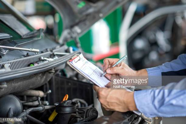 mechanic holding a clipboard of service report working in garage. car repair service. - spare part stock pictures, royalty-free photos & images