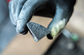 Mechanic holding a pice of broken catalytic converter