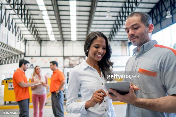 mechanic holding a tablet computer talking to a woman about her car at a garage - lifestyle concepts - auto repair shop stock pictures, royalty-free photos & images