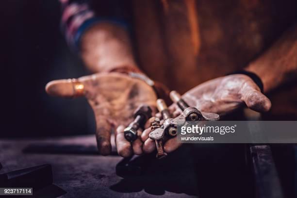 mekaniker som håller olika typer av skruvar i smutsiga händer - don smith bildbanksfoton och bilder