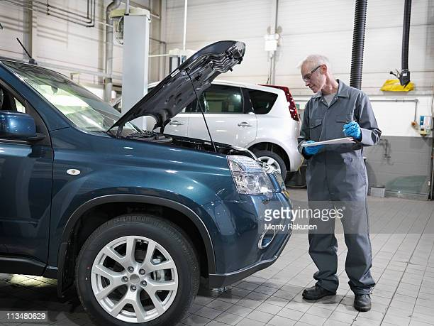 mechanic in car dealership workshop standing by car, with open bonnet, holding pen and paper, analyzing engine - hood clothing stock pictures, royalty-free photos & images