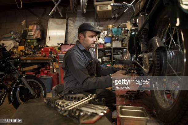 mechanic in his garage converting gas powered motorcycles to bio-diesel - heshphoto - fotografias e filmes do acervo