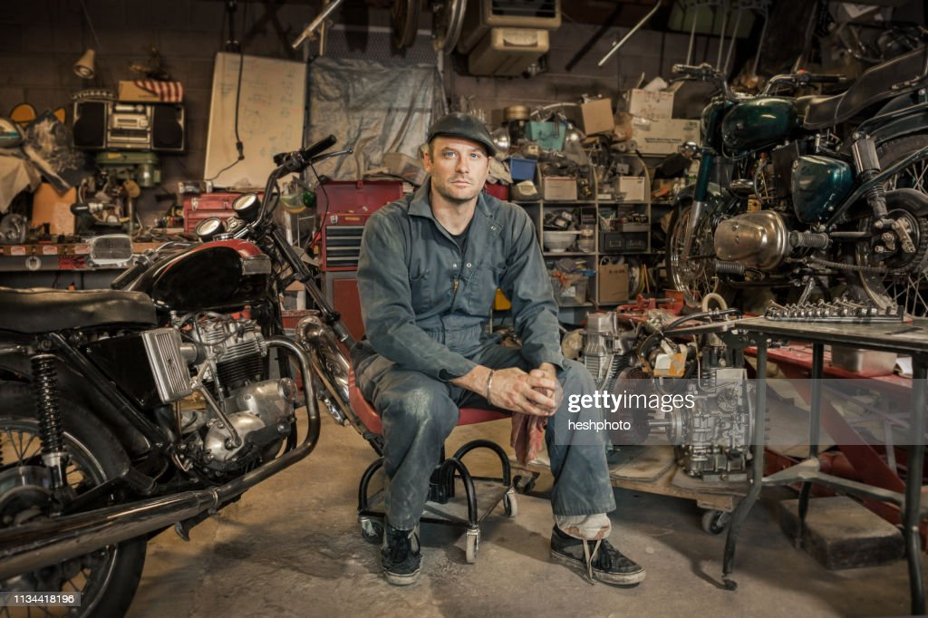 Mechanic in his garage converting gas powered motorcycles to Bio-Diesel : Stock Photo