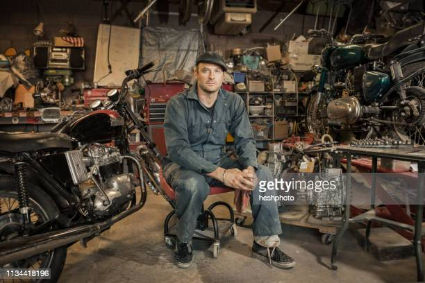 mechanic in his garage converting gas powered motorcycles to bio-diesel - mechanic stock pictures, royalty-free photos & images
