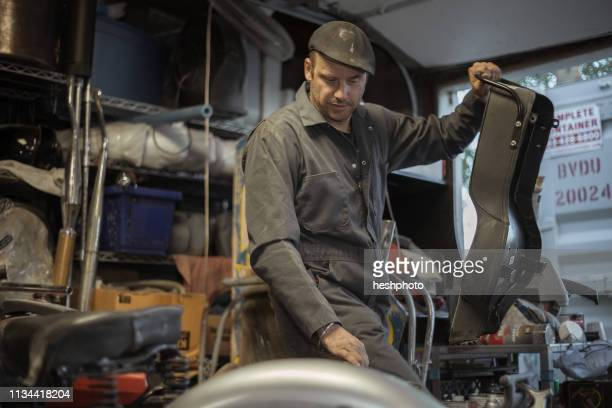 mechanic in his garage converting gas powered motorcycles to bio-diesel - heshphoto stockfoto's en -beelden