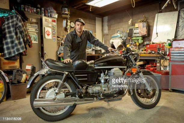 mechanic in his garage converting gas powered motorcycles to bio-diesel - heshphoto - fotografias e filmes do acervo