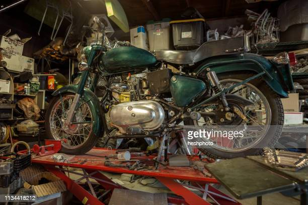 mechanic in his garage converting gas powered motorcycles to bio-diesel - heshphoto stock pictures, royalty-free photos & images