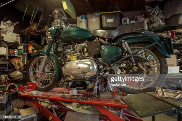 mechanic in his garage converting gas powered motorcycles to bio-diesel - heshphoto stock-fotos und bilder