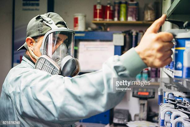 mechanic in protective workwear chooses colors for airbrush
