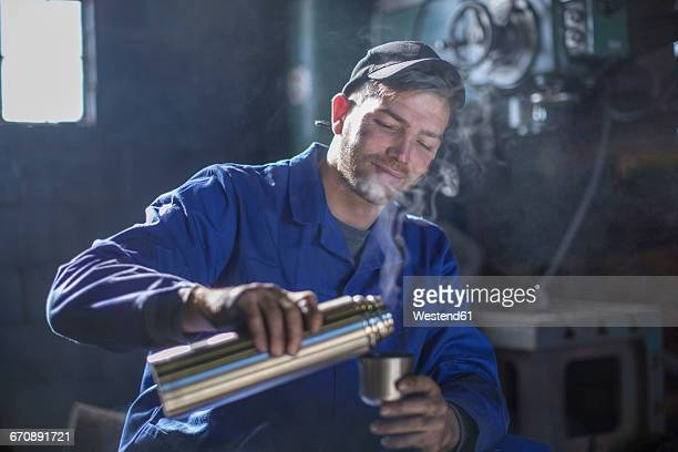 Mechanic in workshop having coffee break